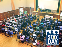 group gathered in auditorium and stay day logo
