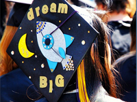 "graduate in cap that says ""dream big"""
